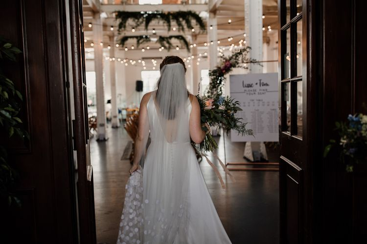 Bride wearing polka dot veil walking in reception with hanging foliage decor and festoon lighting