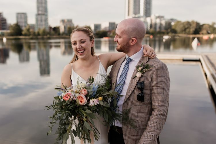 Bride and groom embrace at London celebration with colourful floral bouquet of David Austin roses