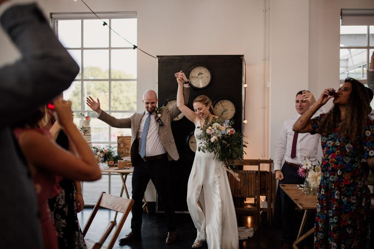 Bride wearing split front gown and groom enter reception with festoon lighting