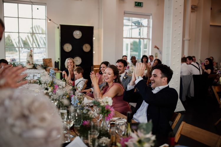 Guests celebrating at city wedding with floral table decor and informal family style dining