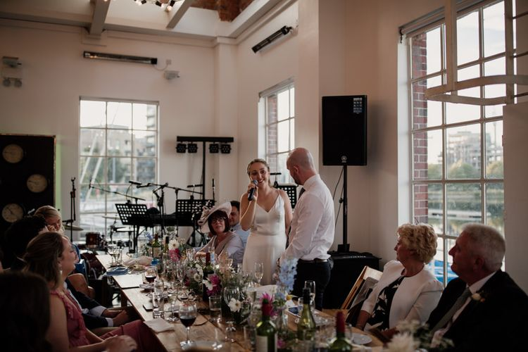 Bride and groom celebrating at city wedding with floral table decor and informal family style dining
