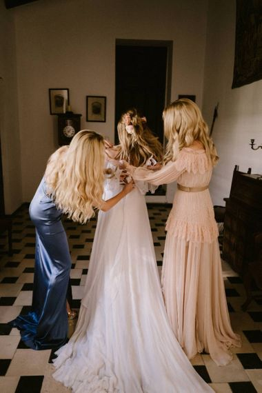 Bride being Helped into Her Wedding Dress by  Bridesmaids