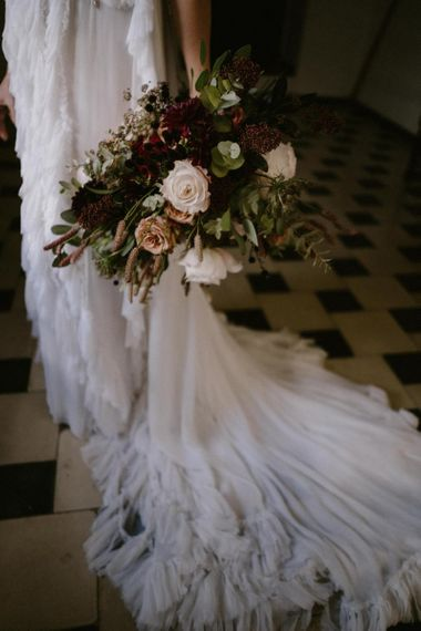 Bride Holding Her Deep Burgundy and Pink Wedding Bouquet nest to Her Romantic Wedding Dress