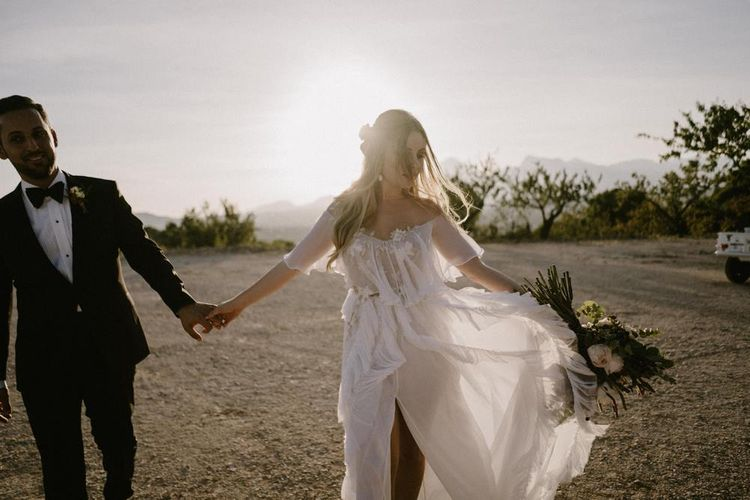 Bride in Ruffles Wedding Dress and Groom in Black Tuxedo Holding Hands During Golden Hour