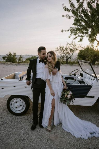 Stylish Bride and Groom Embracing at The Side of Their Jeep Wedding Car