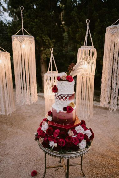 Red and White Wedding Cake with Macrame Detail in Front of Hanging Macrame Chandelier Backdrop