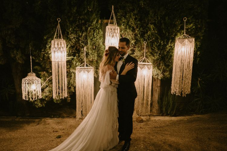 Bride in Otilia Brailoiu - Penelope Wedding Dress and Groom in Tuxedo in Front of Hanging Macrame Chandelier Backdrop