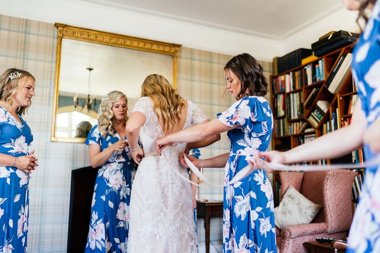 Wedding Morning Bridal Preparations with Bride in Lace wedding Dress and Bridesmaids in Floral Dresses