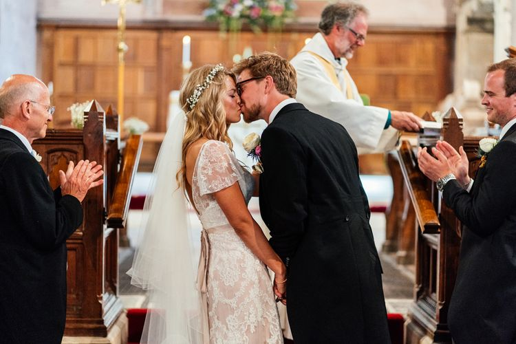 Bride in Lace Essence of Australia Wedding Dress and Groom in Morning Suit  Kissing at the Altar