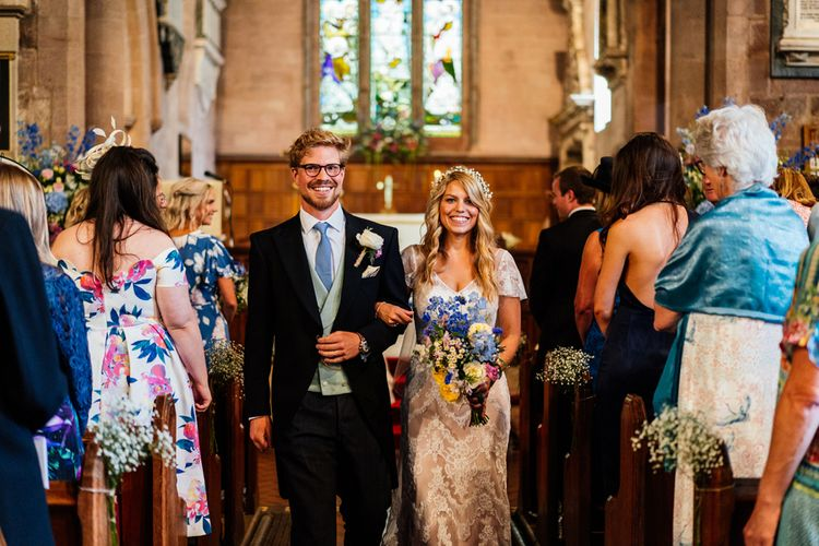 Bride in Lace Essence of Australia Wedding Dress and Groom in Morning Suit Walking Up The Aisle as Husband & Wife