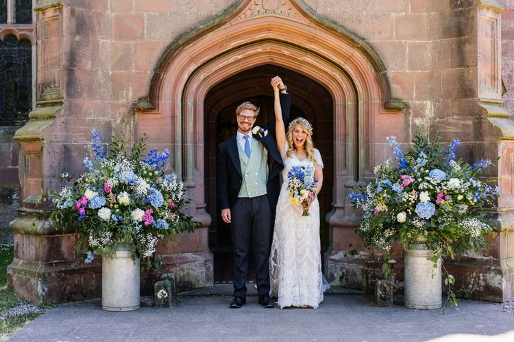 Bride in Lace Essence of Australia Wedding Dress and Groom in Morning Suit Exiting the Church with Pink and Blue Wildflower Filled Milk Churns