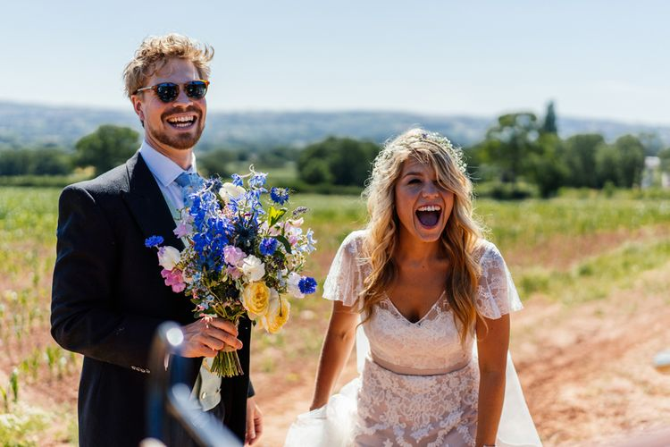 Bride in Lace Essence of Australia Wedding Dress and Groom in Morning Suit Holding Wildflower Bouquet Laughing Together
