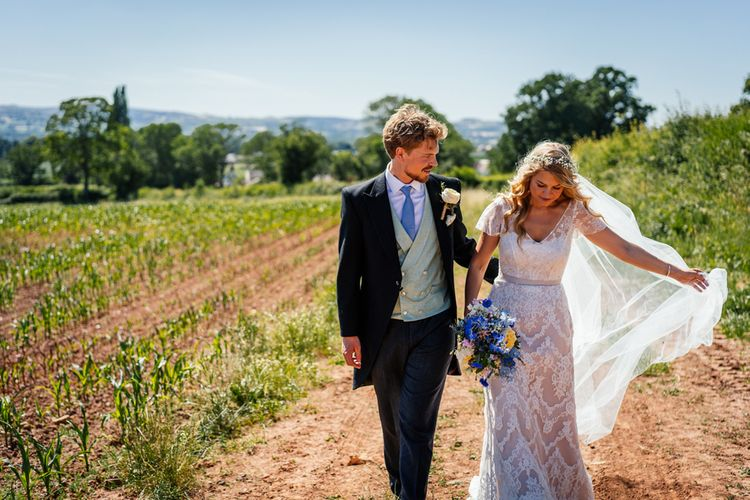 Bride in Lace Essence of Australia Wedding Dress and Groom in Morning Suit Walking Through Fields