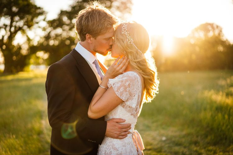 Bride in Essense of Australia Wedding Dress and Groom in Tails Kissing During sunset