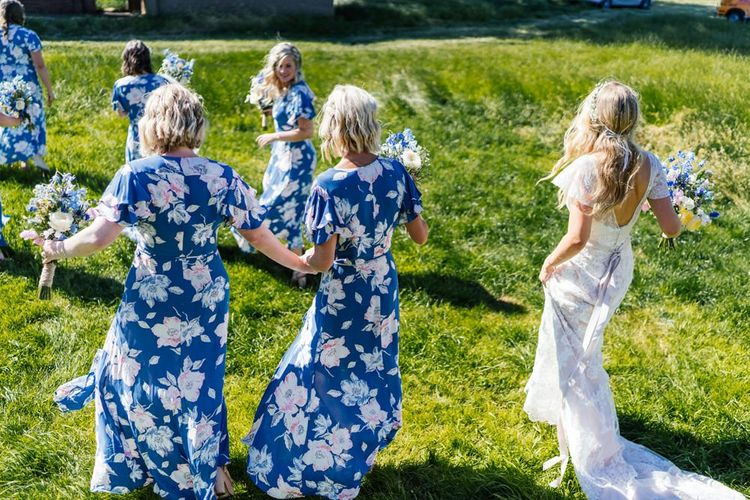 Bridal Party Walking Through a Field in Blue Floral Bridesmaid Dresses from French Connection and Lace Essense of Australia Wedding Dress
