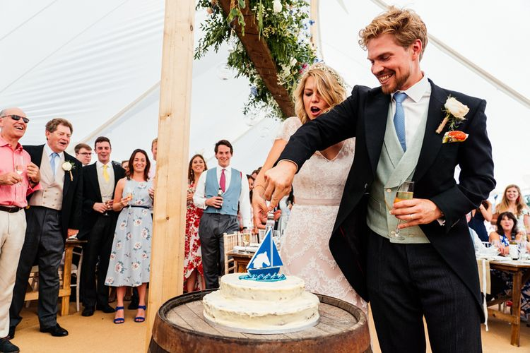 Bride and Groom Cutting the Cake on a Wooden Barrel