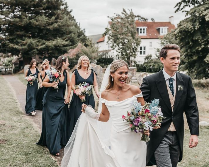 Bride in Halfpenny London wedding dress in church courtyard