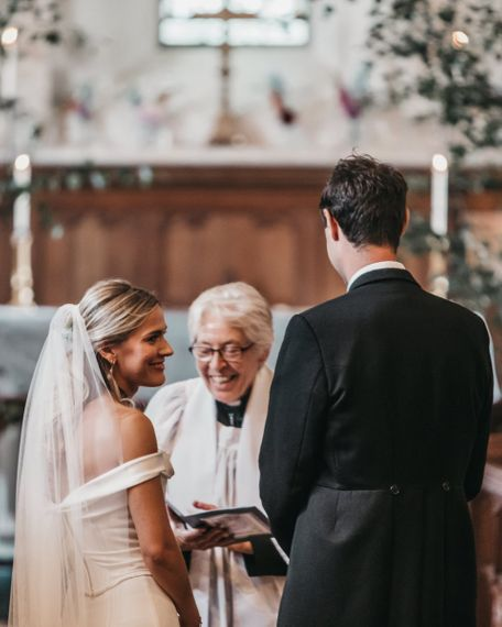 Bride and groom exchange vows during church wedding ceremony
