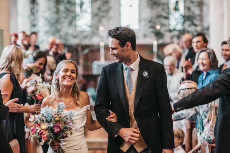 Bride and groom walk up the aisle as husband and wife after church wedding ceremony