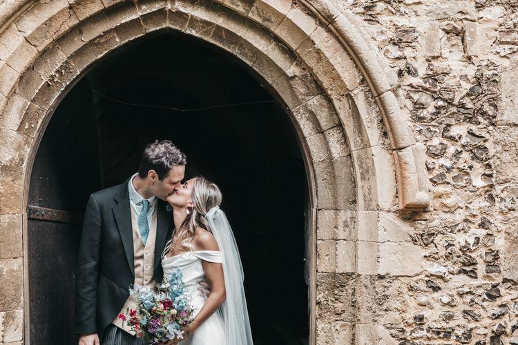 Groom in morning suit kisses his bride at church wedding door