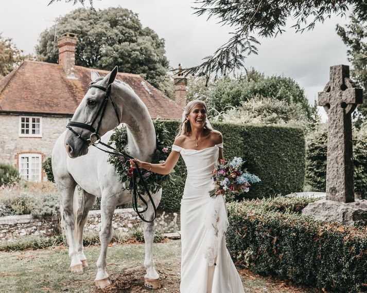 Bride in Bardot wedding dress and her pet horse with flower collar