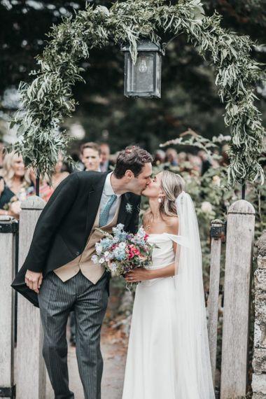 Bride and groom kissing at local church gates