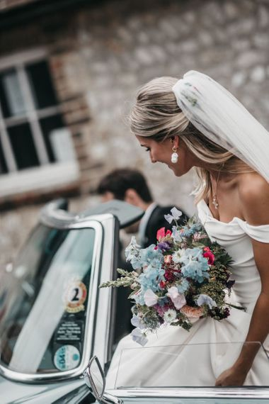 Bride holding a blue and pink wild flower bouquet  gets into the wedding car
