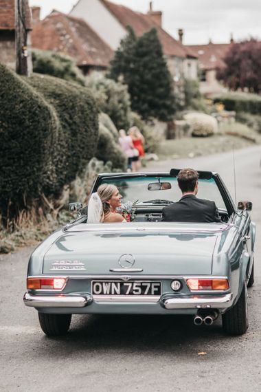 Bride and groom drive off in a blue convertible wedding car