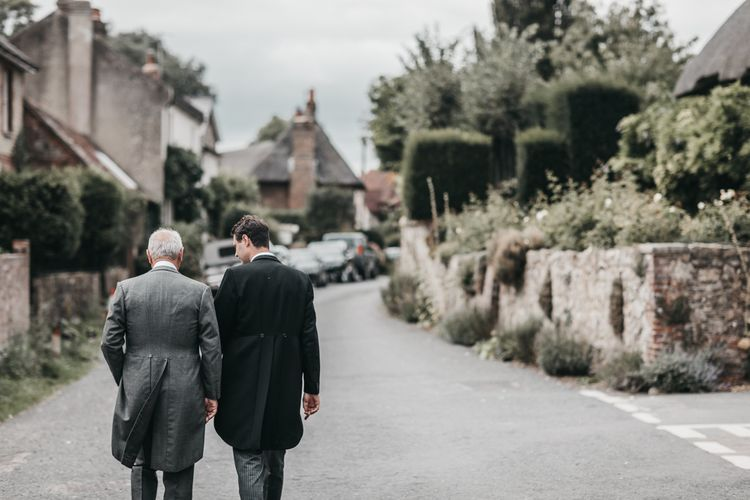 Groom and father of the groom walking down a country lane in traditional morning suit