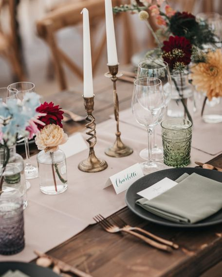 Colour plate setting with gold candlesticks, coloured tableware and bright wedding flowers