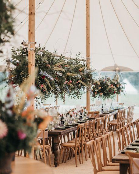 Wild flower installation above wooden tables