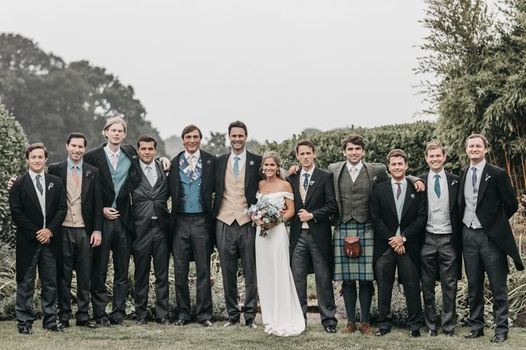 Groomsmen in different traditional morning suits for church wedding