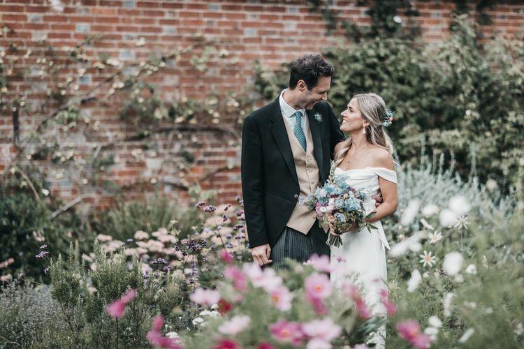 Bride and groom portrait amongst a wildflower garden