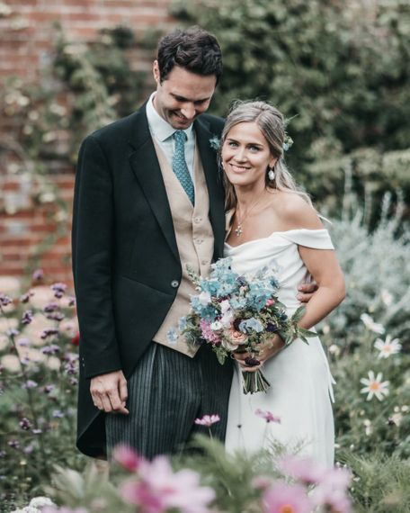Bride and groom embracing in morning suit and Halfpenny London wedding dress for church wedding
