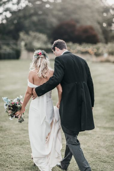 Groom in tails with his arm around his bride in a Bardot wedding dress