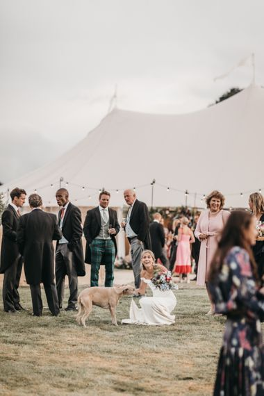 Bride in off the shoulder wedding dress stroking her pet dog during outdoor reception