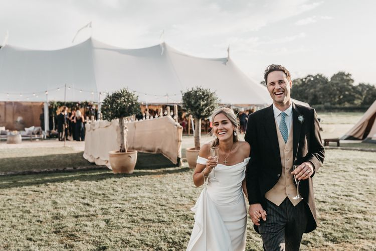 Bride and groom enjoying a drink at their outdoor Sperry tent reception