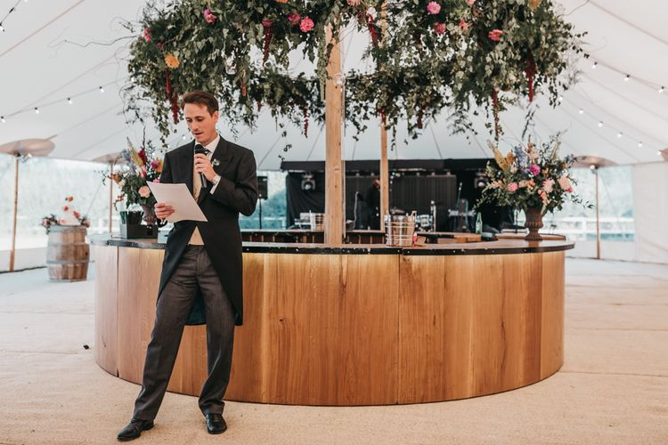 Best man delivering the wedding speech in front of the wooden bar
