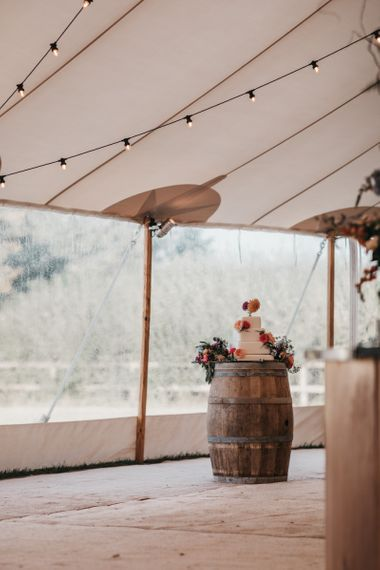 Wedding cake resting on a wooden barrel in the PapaKata Sperry tent reception