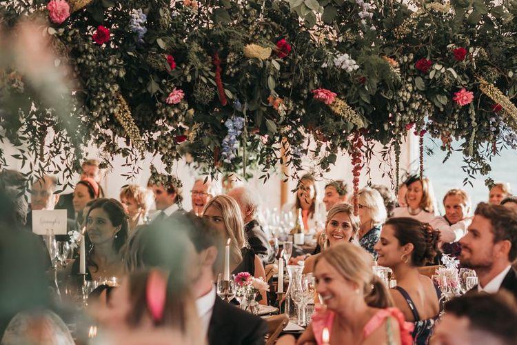 Wedding guests sitting under a wildflower installation