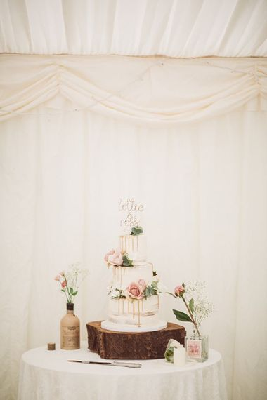 Tiered Drip Wedding Cake Surrounded by Flowerstem in Bottles