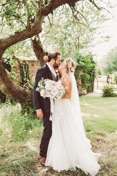 Bride and Groom Kiss holding Blush Bouquet