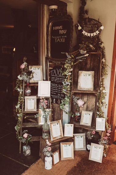 Rustic DIY Table Plan with Photoframes with Flowerstems in Bottles