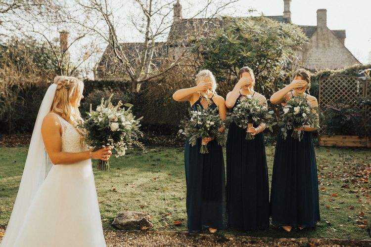 Bridesmaids in navy dresses first look of the bride