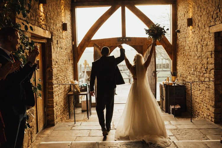 Bride and Groom exiting Cripps Barn after their November wedding  ceremony