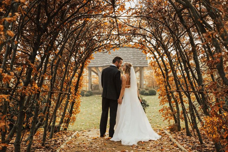 November wedding portrait with brown leaf tunnel