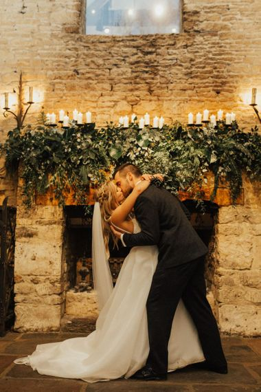 Bride and groom kissing in from of the fireplace at Cripps Barn