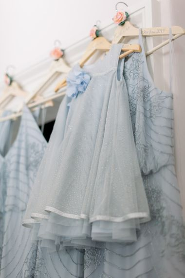 Blue flower girl and bridesmaid dresses hanging up