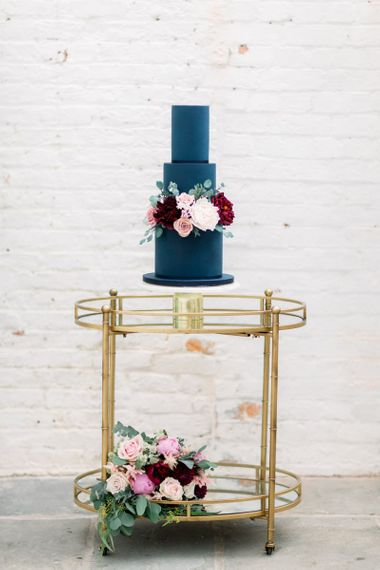Navy wedding cake with pink and flowers sitting on gold trolley