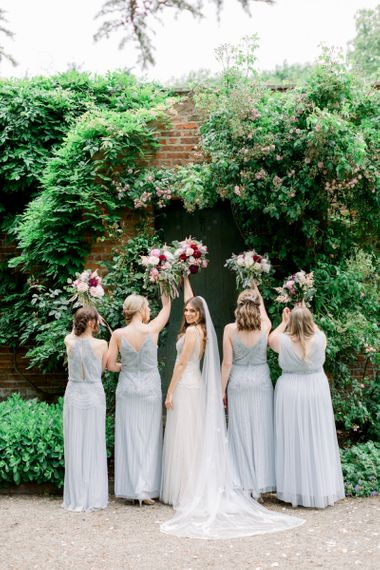 Bridal party portrait holding their bouquets in the air
